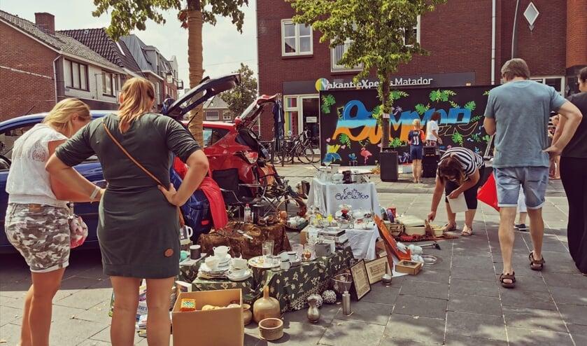 Ook particulieren boden spullen aan vanuit de kofferbak. Op de achtergrond wordt samen met kinderen gewerkt aan een graffiti. Foto: Janette van Egten