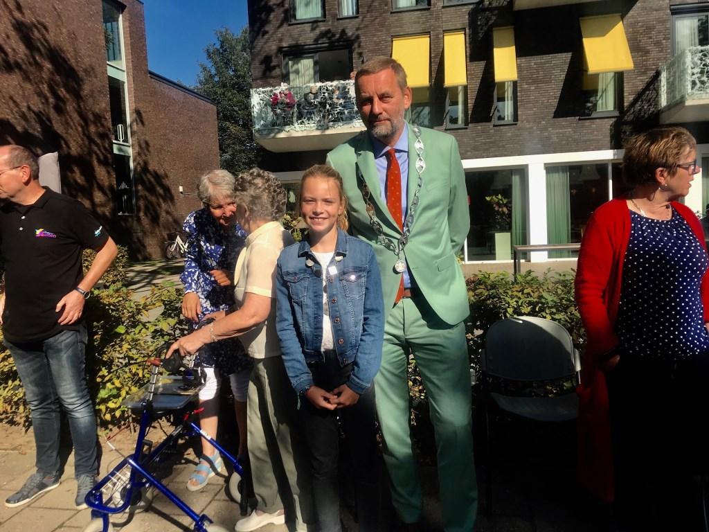 Burgemeester  Anton Stapelkamp en kinderburgemeester Rosanne Lohuis zwaaien samen naar mensen tijdens de bloemencorso. Foto: Eva Schipper  © Achterhoek Nieuws b.v.