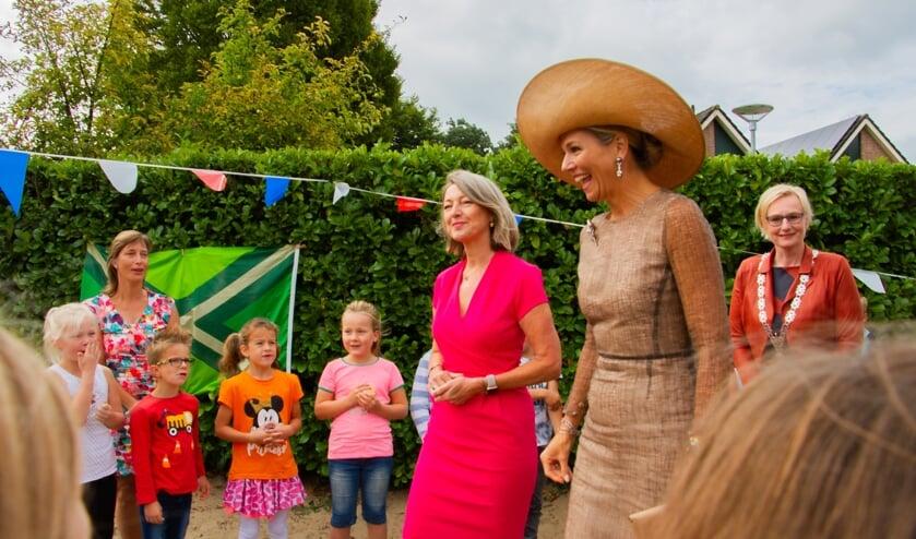 Gastvrouw Ineke Dezentjé, koningin Máxima en burgemeester Marianne Besselink lopen over het schoolplein van basisschool De Rank tussen de zingende kinderen door. Foto: Liesbeth Spaansen
