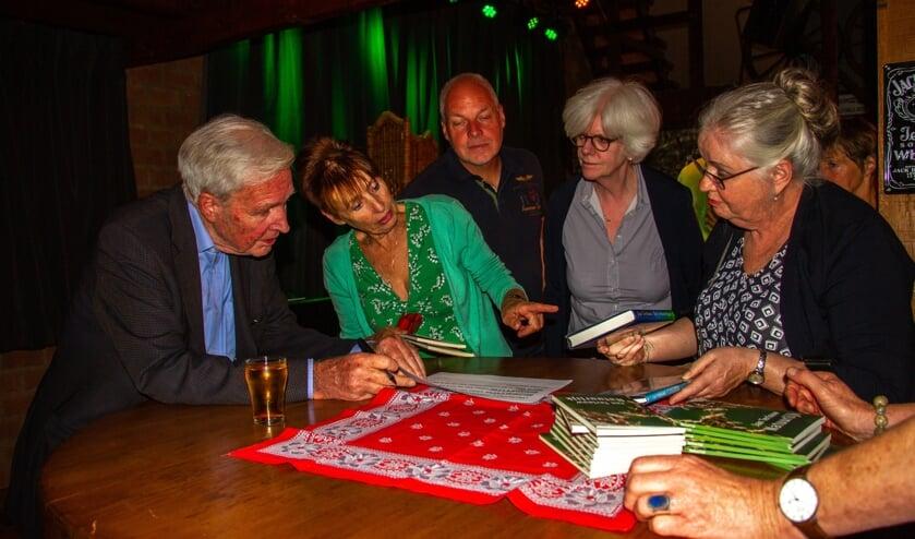 Jan Terlouw (l.) signeert boeken tijdens de jubileummiddag van de Flopbieb in Toldijk. Foto: Liesbeth Spaansen