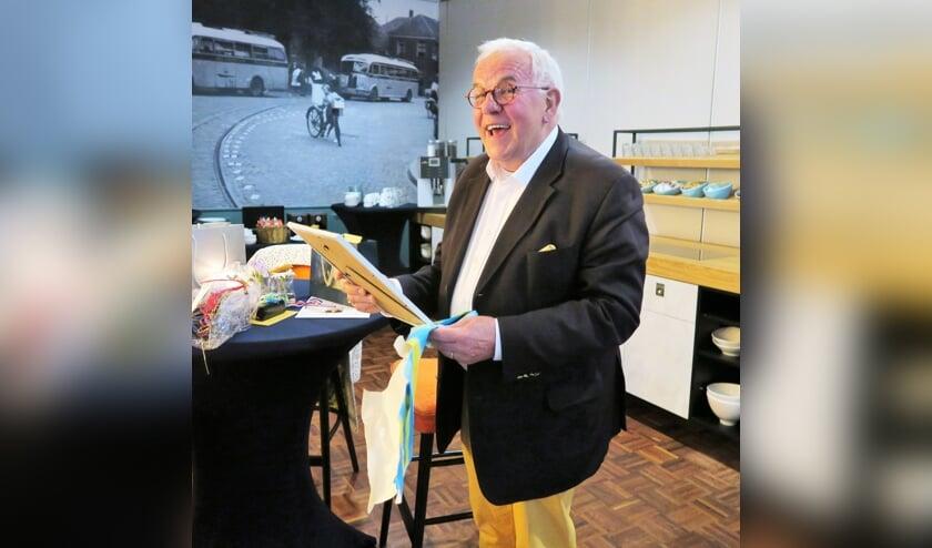 Henk Nijhoff bewondert zijn zojuist ontvangen afscheidscadeaus. Foto: Theo Huijskes
