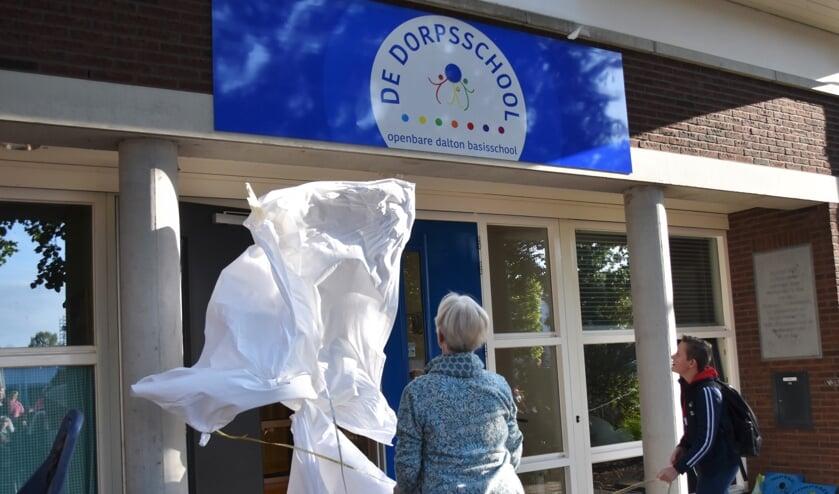 De taak van Leontine en Wessel zit erop. Het nieuwe logo van De Dorpsschool is onthuld. Foto: Alice Rouwhorst