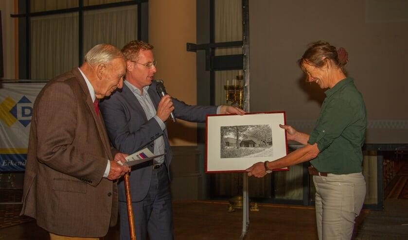 Wethouder Willem Buunk overhandigt de cheque aan Jan Markvoort en de pentekening van de eekschuur aan dochter Elisabeth. Foto: Liesbeth Spaansen