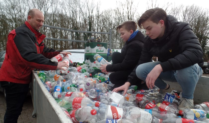 Ard, Dennis en Jacco Kettelerij bij hun ingezamelde 'berg' lege flessen en kratten bier. Foto: Jan Hendriksen.