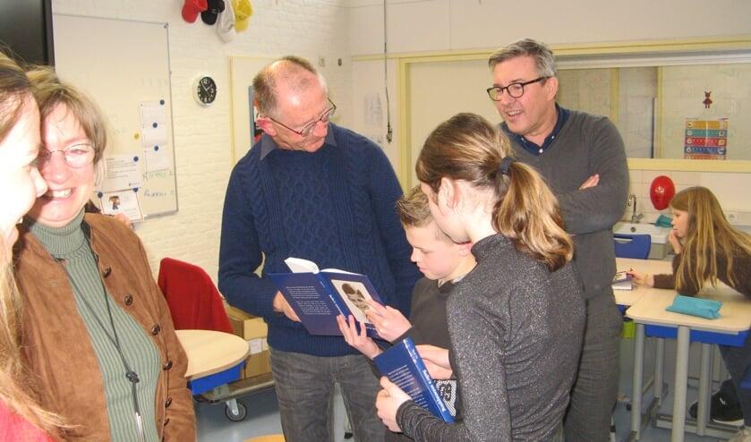 Henk Vis en Jan van der Horst met twee leerlingen die het boekje Sallo's ontsnapping bekijken. Foto: Bart Kraan