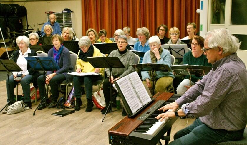 Het koor repeteert onder leiding van Emile Engel. Foto: Ans ter Horst