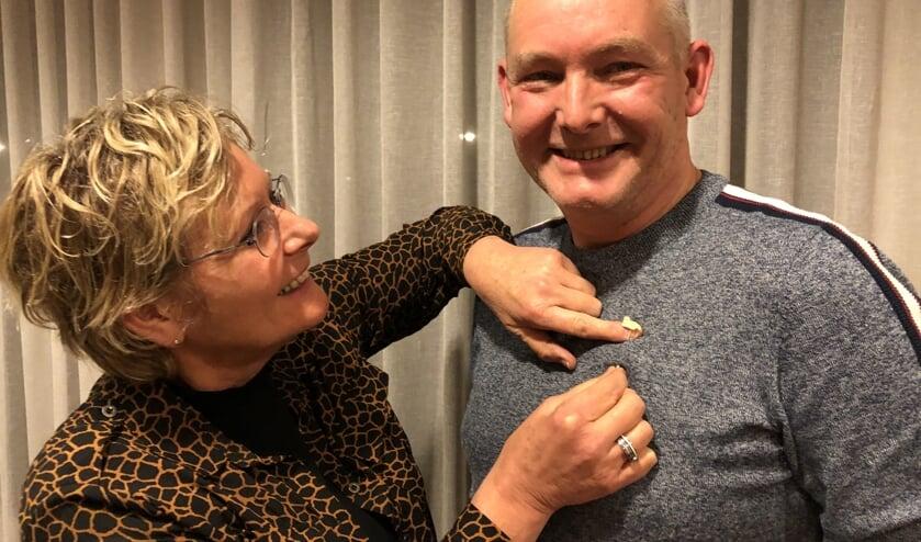 Arnold krijgt de onderscheiding opgespeld door zus Brigitte, ook collega-muzikant. Foto: PR