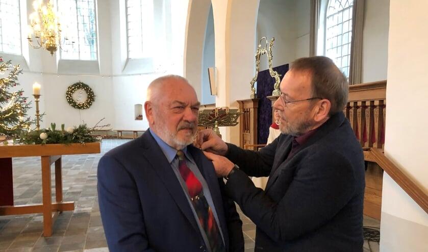 Riek Linde krijgt het draaginsigne in zilver van de Protestantse Kerk opgespeld door kerkrentmeester Luc van Asselt. Foto: PR