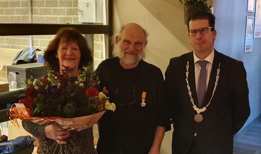 Jan en Ria Krooshof met lintje en bloemen naast burgemeester Joost van Oostrum. Foto: Rob Weeber
