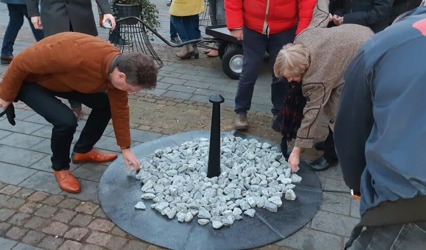 De stenen worden op het tijdelijk monument op de Markt geplaatst. Foto: Ferry Broshuis