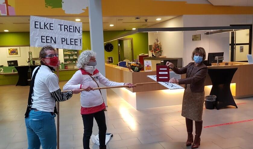 <p>Sandra Gosseling (l) en Greetje van Amstel bieden wethouder Zomer een boek vol handtekeningen aan: &lsquo;Elke trein een plee.&rsquo; Foto: Han van de Laar </p>