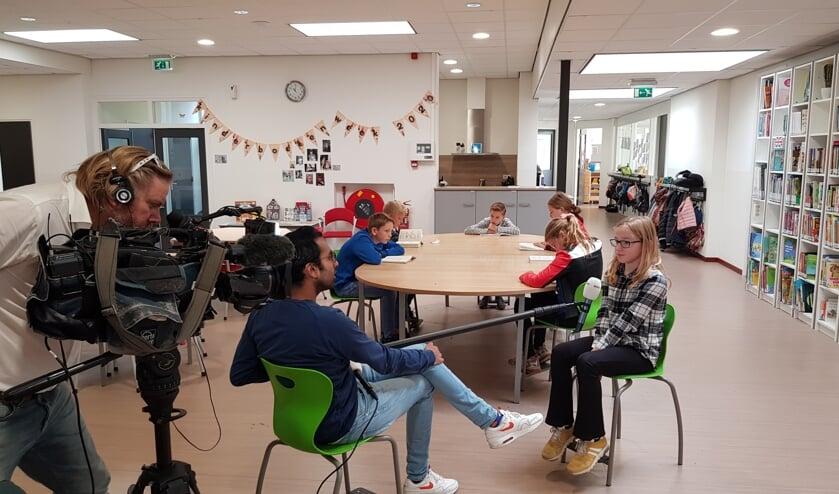 Cameraman Bjarne, verslaggever Ruwan en de kinderen Britt, Anniek, Naomi, Trysten, Menno en Dylan tijdens de opnames van het Jeugdjournaal met rechts de bibliotheek. Foto: Han van de Laar