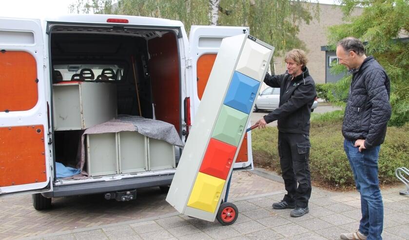 <p>Congiërge Gerard Ligtlee laadt de kleurrijke lockerkastjes uit onder toeziend oog van penningmeester Bart van 't Hooft. Foto: Annekée Cuppers</p>