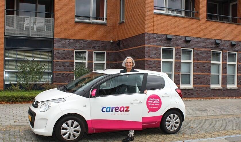<p>Liedy Vennegoor met een auto met het nieuwe logo. Foto: PR</p>
