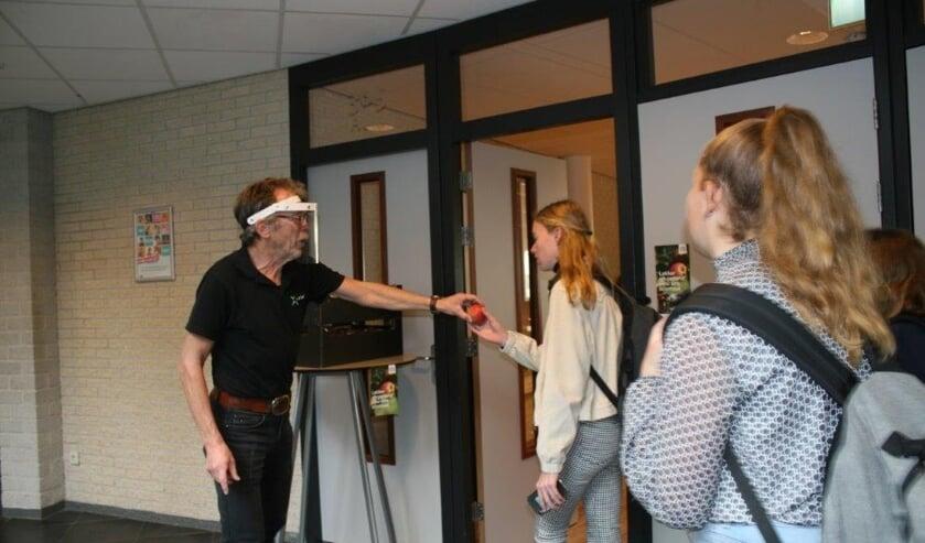 <p>Conciërge Henry Hummelink deelt LTO appels uit op het Marianum Lichtenvoorde</p>
