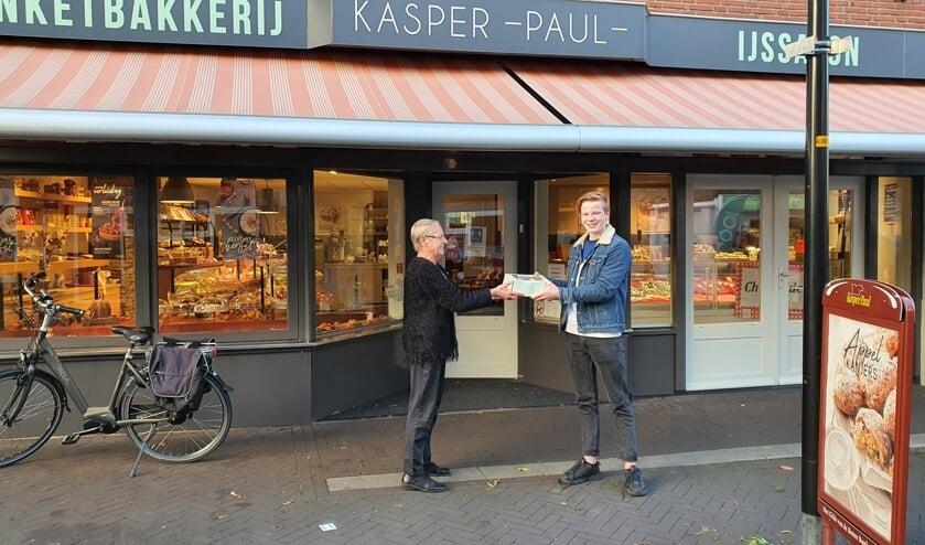 Manus Kamink krijgt de taart van Banketbakkerij Kasper Paul. Foto: PR