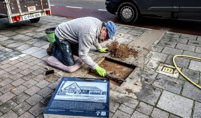 <p>Harry Jansen – voorzitter van de stichting Tegelroute Bronckhorst – maakt plek voor een historische tegel aan de Hummeloseweg in Hengelo, waar in 1937 autogarage Herwers begon. Foto: Luuk Stam</p>