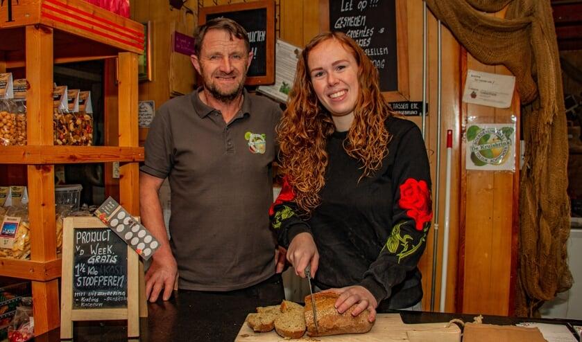 Iris Garritsen snijdt onder toeziend oog van vader Dick, het net afgebakken ambachtelijke brood aan in Boerderijwinkel De Kruisbrink. Foto: Liesbeth Spaansen