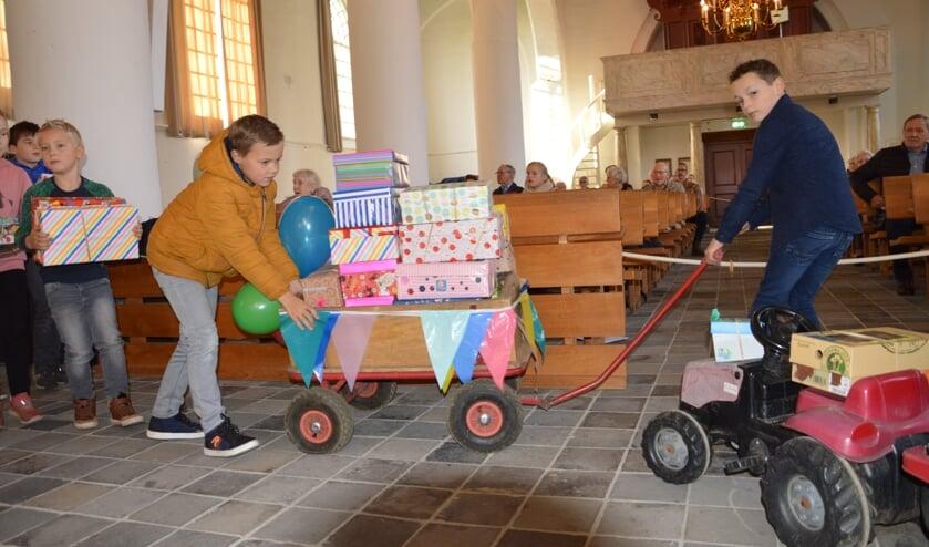 <p>Kinderen brengen de vele schoenendozen in de kerk. Het totaal kwam uit op 195 dozen. Foto: Marlies Groeneveld</p>