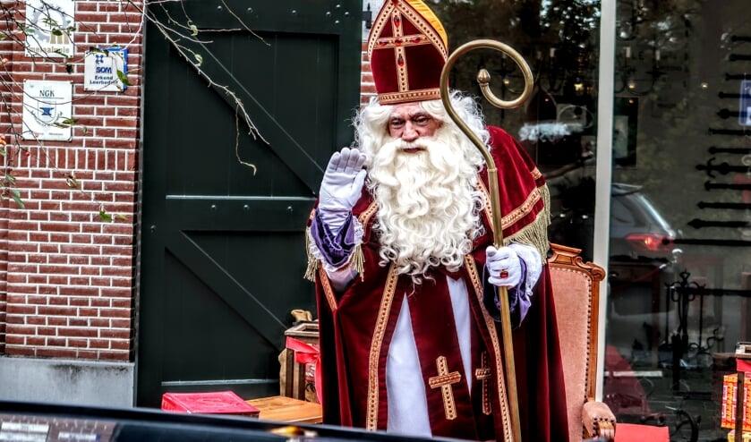 <p>Sinterklaas zwaait de hele middag naar de kinderen die in auto's langs hem rijden tijdens de Sinterklaas-drive through. Foto: Luuk Stam</p>