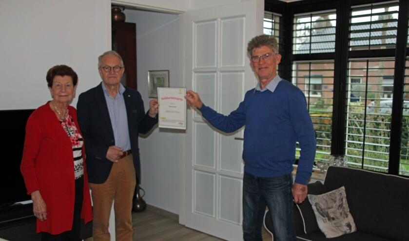 <p>PP-voorzitter Gerrit Stronks (rechts) overhandigt Theo Heesen de oorkonde. Links Joke Heesen. Foto: Lydia ter Welle</p>