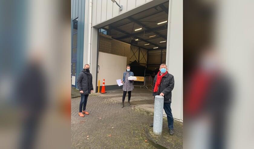 Wethouders Jorik Huizinga (links) uit Doetinchem en wethouder Joop Wikkerink (rechts) uit Aalten brengen oliebollen in de teststraat in Winterswijk. Foto: PR