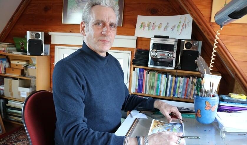 <p>Peter van Harmelen in zijn atelier met een tekening waar hij enkele dagen aan heeft gewerkt. Foto: Arjen Dieperink</p>
