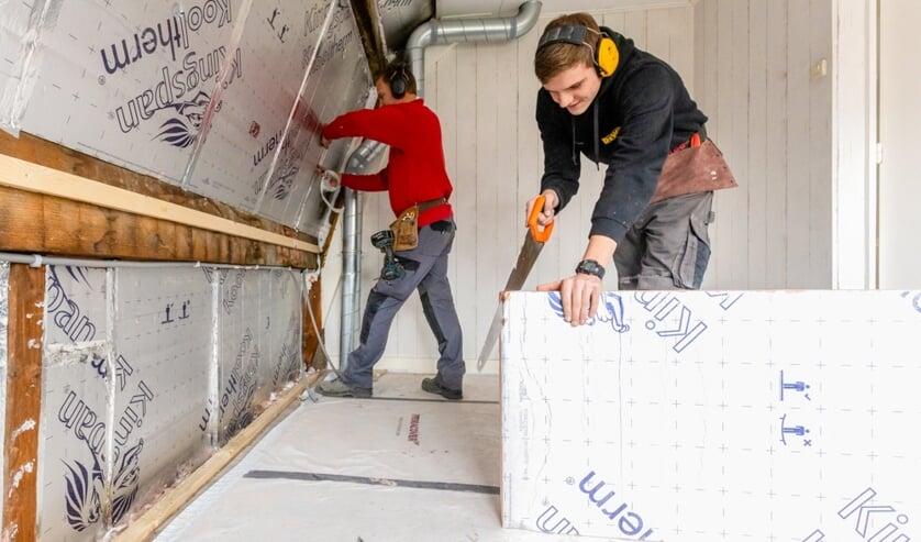 Foto: Medewerkers van aannemersbedrijf Kormelink brengen isolatiemateriaal aan tijdens de verduurzaming van een leegstaande woning. Foto:Nicole Tanke, Lines Are Everywhere