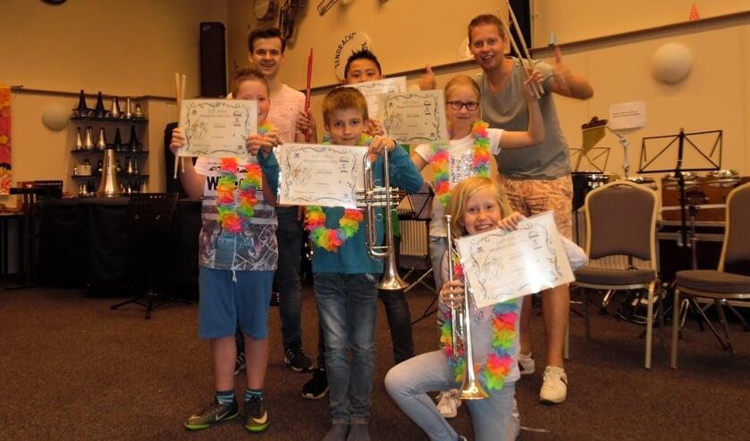 Oud-leerlingen muziek maak je zelf met hun behaalde diploma's en docenten Mart Ebbers en Bas Konings. Foto PR