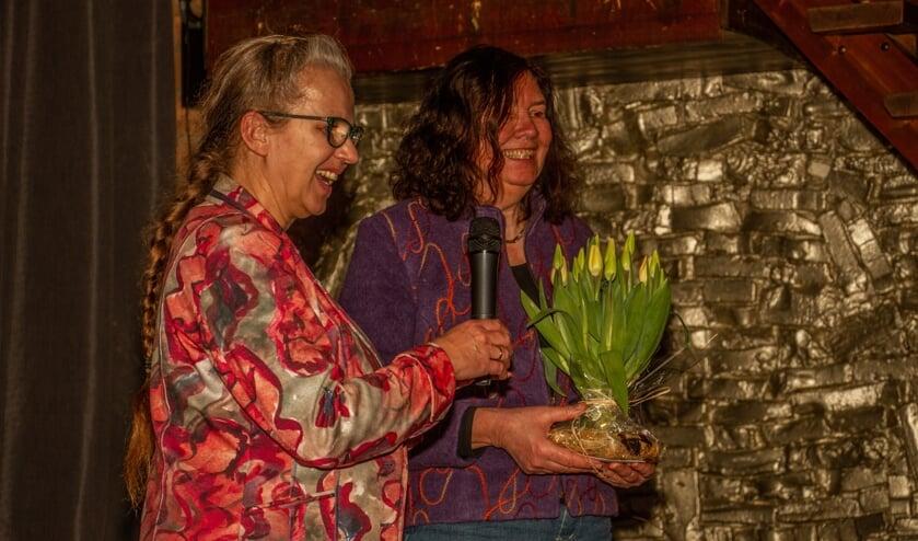 Schrijfster Alice Garritsen krijgt van Alien Maalderink een schoof tulpen. Foto: Liesbeth Spaansen