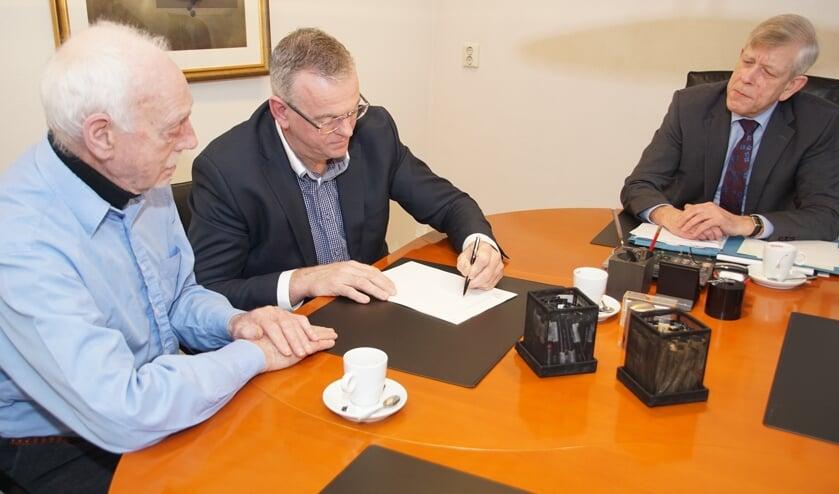 Onder toeziend oog van notaris Moerland (rechts) ondertekenen Leo Gensen en Jan Steverink (midden) de akte met de statuten. Foto: Frank Vinkenvleugel