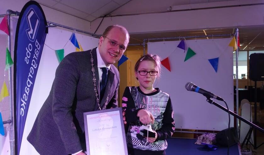 Naomi krijgt een onderscheiding en een kettinkje. Foto: Clemens Bielen