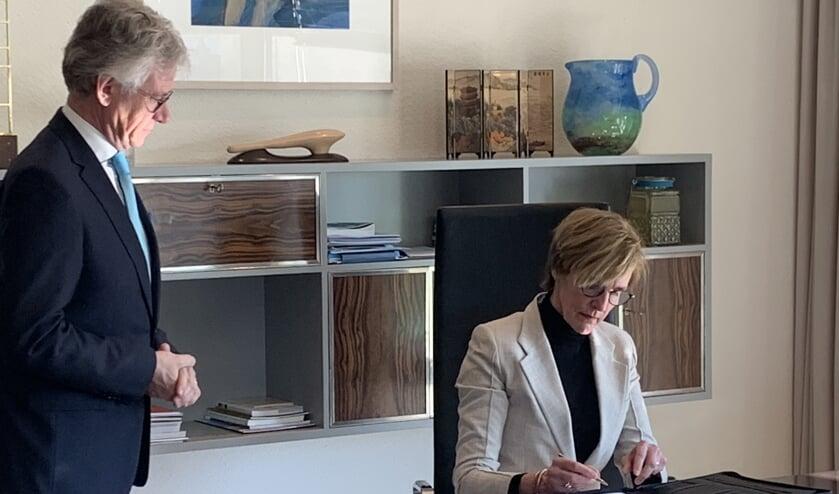 Onder toeziend oog (en op gepaste afstand) van Commissaris van de Koning John Berends, ondertekent Annette Bronsvoort haar herbenoeming tot burgemeester van Oost Gelre.