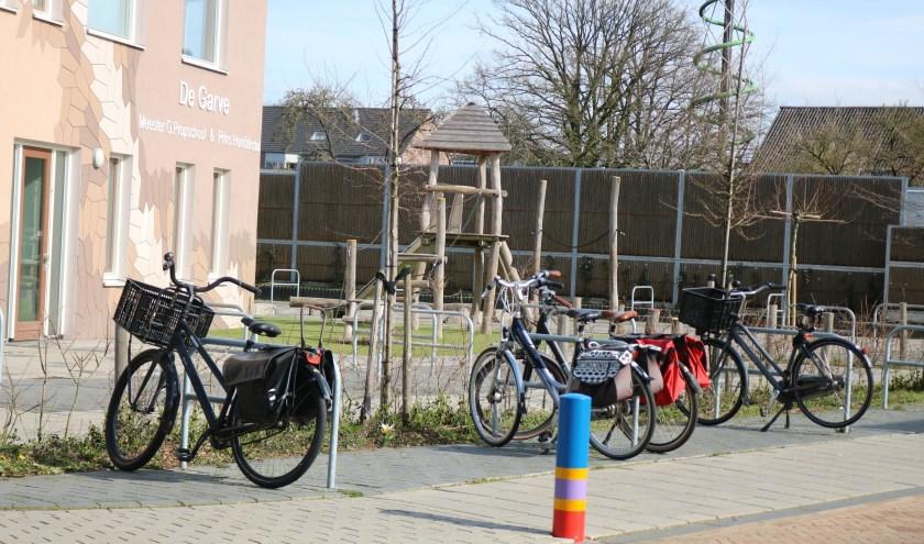 Lege speeltoestellen en enkele fietsen van de leraren bij school. Foto: Arjen Dieperink