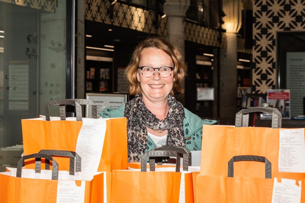 Bibliotheekmedewerkster bij de tassen met af te halen boeken. Foto: Henk Derksen  © Achterhoek Nieuws b.v.