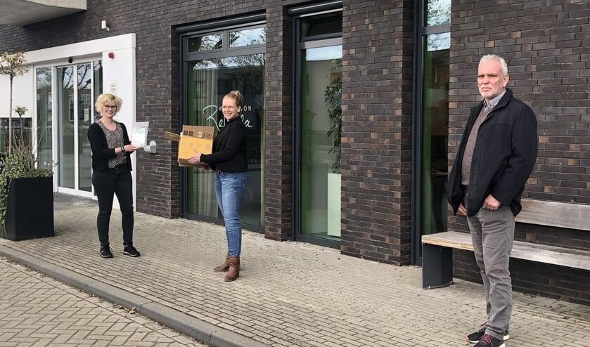 De mondkapjes worden door Petra Kastein en Henk Haaring overhandigd aan Dagmar Schenk. Foto: PR