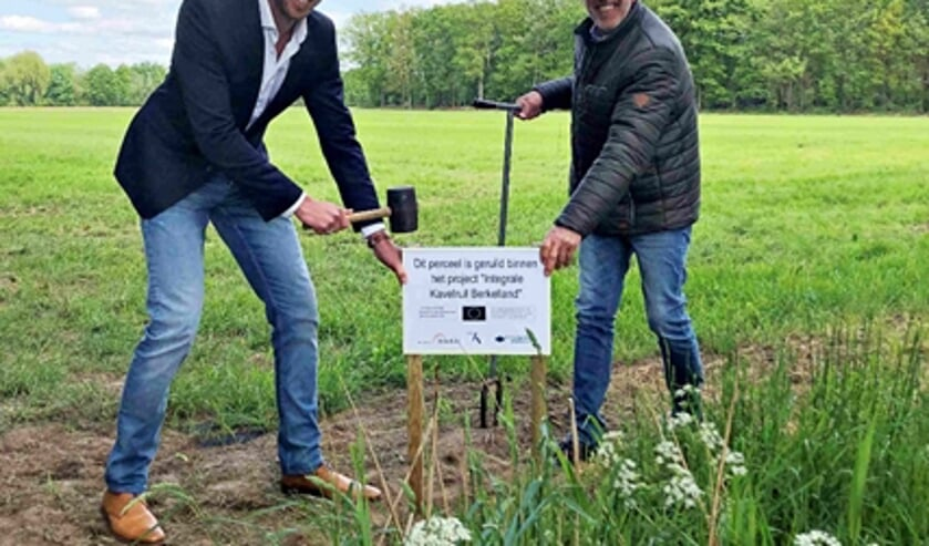 Wethouder Maikel van der Neut en Bertus Hesselink plaatsen het bord. Foto: gemeente Berkelland