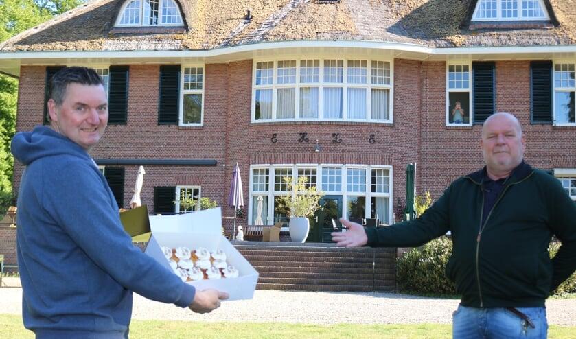 Bakker Wijnand Stegeman biedt zorgdirecteur Henk Boelen (rechts) de doos met gebak aan. Foto: Arjen Dieperink