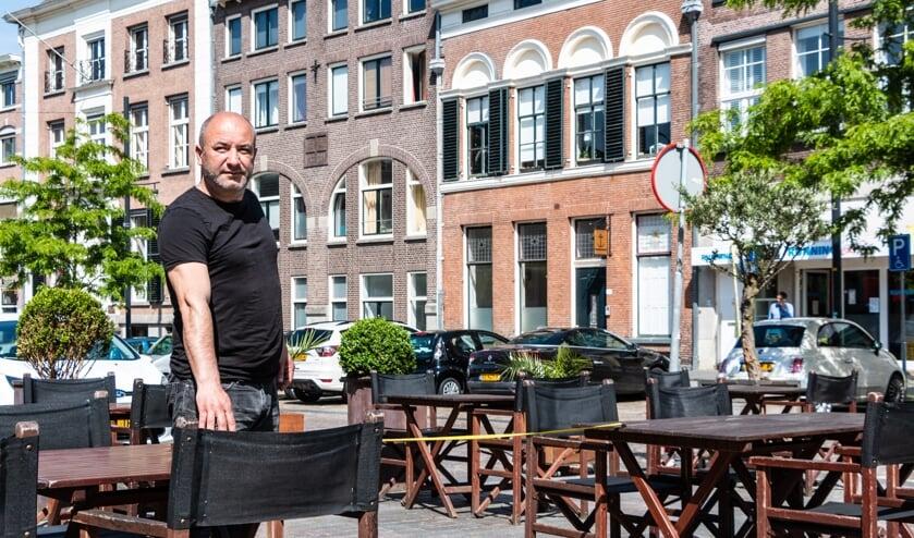 De heer Kavak van Restaurant Rocca controleert de afstand tussen de tafeltjes met een meetlint. Foto: Henk Derksen