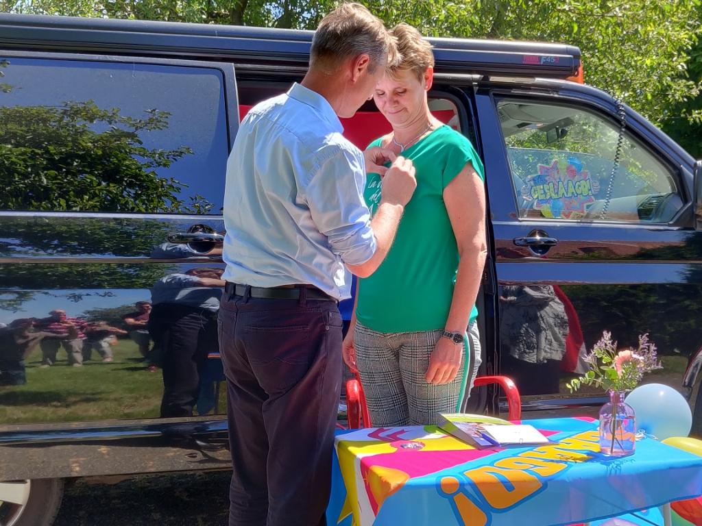 Karin krijgt het insigne opgespeld door haar man. Foto: Rob Stevens  © Achterhoek Nieuws b.v.