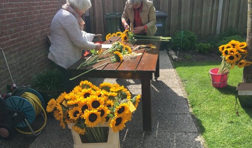 Kaartjes met de wens 'Goed gaon' worden aan de zonnebloemen geknoopt. Foto: Trudi van der Weijden