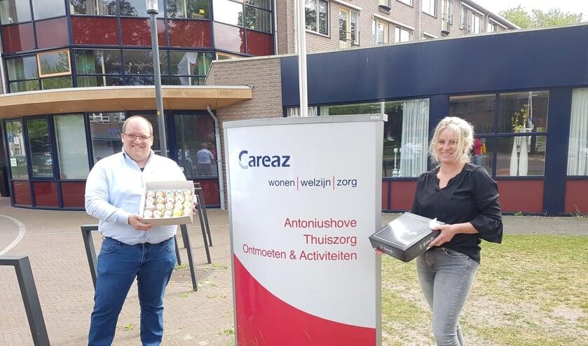 Geert-Jan Scholtz, bedrijfsleider Obbink Lichtenvoorde, en Manon Huinink, welzijnscoach Careaz, met twee dozen gebakjes voor de bewoners van de Antoniushove in Lichtenvoorde.