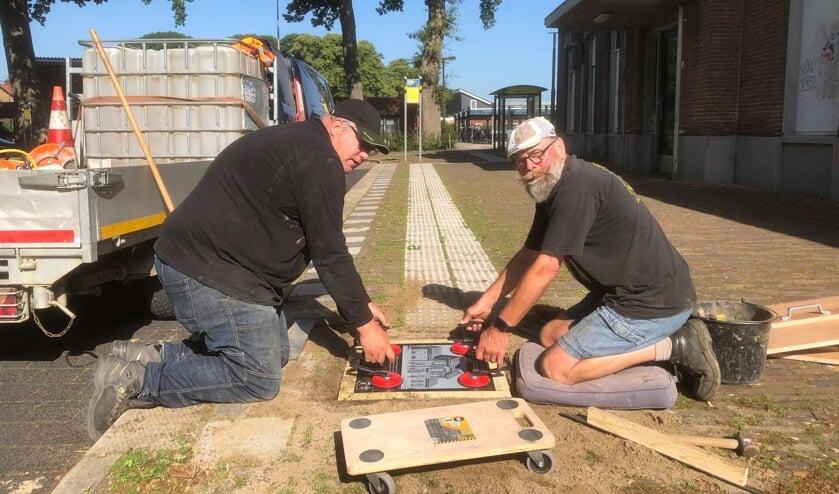 Een tegel wordt gelegd door Frank Sessink (l) en Harry Jansen. Foto: Stichting Tegelroute  Bronckhorst