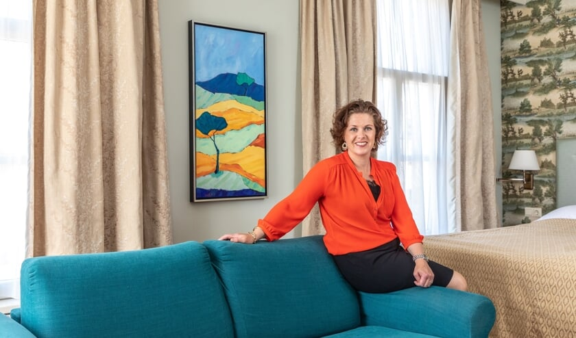 """Elisabeth Remmelink in een van de hotelkamers bij een kunstwerk van Henk Hulshof: """"Het werk moet me een goed gevoel geven en de ruimte net wat meer karakter."""" Foto: Bas Weetink"""