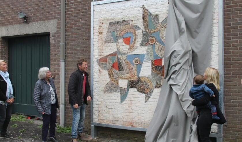 'Jenni, Minie, en Jan Derk Heesen (vlnr) kijken toe hoe hun (klein)dochter met haar zoon het mozaïek van Ger Heesen onthult.  foto Lineke Voltman
