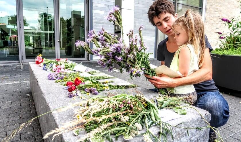 Maaike Kuyk uit Vorden kwam zondag samen met haar dochtertje Elaine naar het gemeentehuis van Bronckhorst in Hengelo om met bloemen haar stem tegen de coronamaatregelen te laten horen. Foto: Luuk Stam