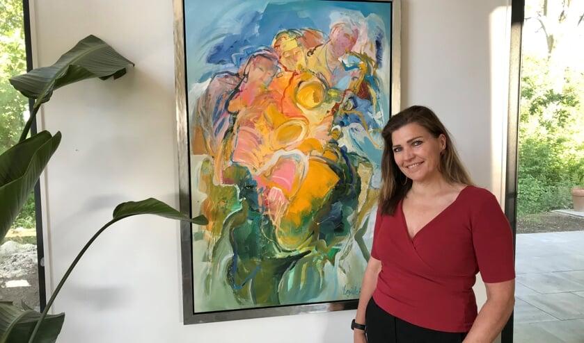 """Manon Bagijn is blij met het kunstwerk dat ze huurt van Kunst of Art. """"Ons huis staat midden in het groen. Dat is eigenlijk al een schilderij op zich. Daarom wilden we juist felle kleuren aan de muur. Kunst maakt je interieur echt af."""" Foto: Manon Bagijn"""