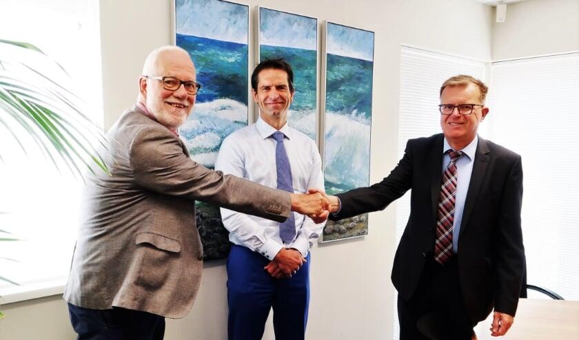 Hans Scheinck (rechts) en Harry Paf (links) feliciteren elkaar met de officieel beklonken fusie. In het midden notaris Edwin Roerdink. Foto: Theo Huijskes