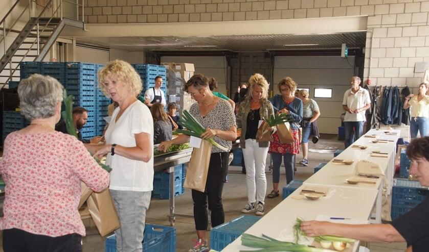 De deelnemers pakken de spullen die ze nodig hebben voor hun 'bloemschikopdracht' met prei. Foto: Frank Vinkenvleugel