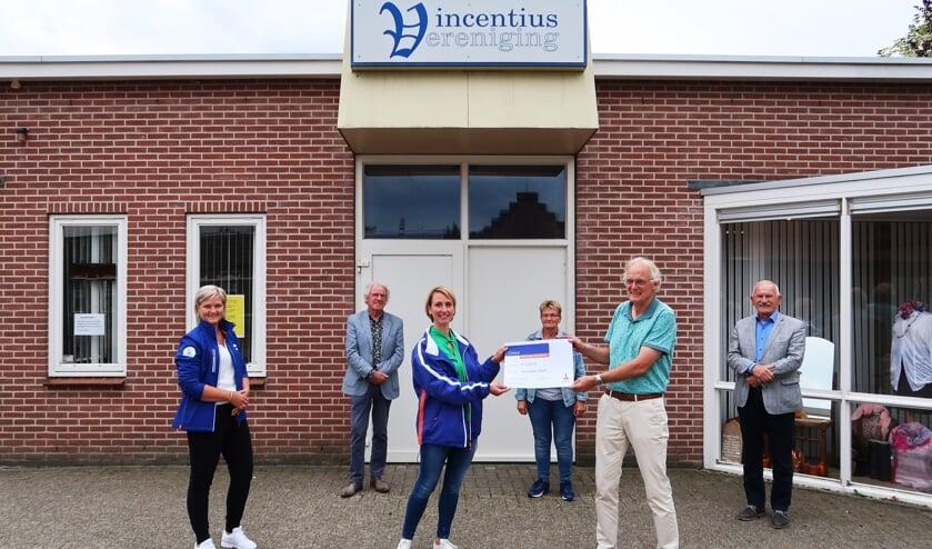 Gerard Kamp, voorzitter van de Vincentiusvereniging, neemt de Rabo-cheque in ontvangst van Marrit Heuzinkveld, terwijl Petra ter Bogt (geheel links) toekijkt. Foto: Theo Huijskes